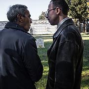 Mohamed et Aldo regarde la pierre tombale d'une autre victime migrante; Mohamed lui explique qu'il voudrait commander une pierre tombale pareille pour son frère Bilal