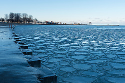 © Licensed to London News Pictures. 04/01/2017. Chicago, USA. Pancake ice floats on the icy shoreline of Lake Michigan at North Avenue Beach in Chicago as a cold spell returns to the Windy City, with daytime high temperatures of -6C.  Sub-zero temperatures are forecast to remain for the rest of the week. Photo credit : Stephen Chung/LNP