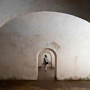 A young woman walks down the a passageway between deserted chambers and bleak beige walls in La Fortaleza in Old San Juan, Puerto Rico.  A U.S. World Heritage Site and National Historic Site, La Fortaleza is maintained and operated by the United States Park Service.