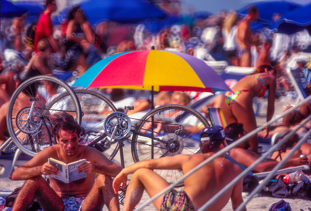 A crowded beach, including a man reading and many sunbathers in South Beach