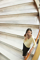 Woman standing on staircase using mobile phone elevated view.