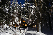 Log cabin at night by moonlight after a snowstorm in winter. Yaak Valley in the Purcell Mountains, northwest Montana.