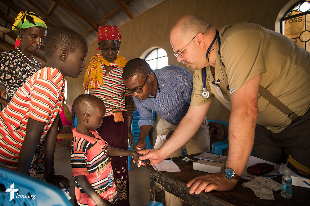 Dr. Jeff Pruitt, a member of St. John Lutheran Church and School in Defiance, Ohio, works with his Kenyan medical colleague as they treat a young patient during the LCMS Mercy Medical Team on Monday, June 20, 2016, in Nataparkakono, a village in Turkana, Kenya.  LCMS Communications/Erik M. Lunsford