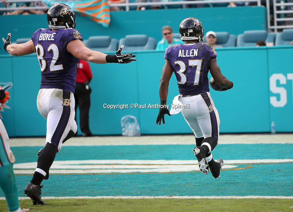 Baltimore Ravens tight end Nick Boyle (82) waves his arms in celebration as Baltimore Ravens running back Javorius Allen (37) coasts over the goal line as he scores on a 41 yard touchdown catch and run pass play that cuts the Dolphins third quarter lead to 15-10 during the 2015 week 13 regular season NFL football game against the Miami Dolphins on Sunday, Dec. 6, 2015 in Miami Gardens, Fla. The Dolphins won the game 15-13. (©Paul Anthony Spinelli)