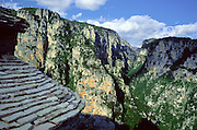 "See Vikos Gorge from the slate Agias Paraskevis Monastery, in Zagoria, north Pindus Mountains (Pindos or Pindhos), Epirus/Epiros, Greece, Europe. Vikos Gorge is the world's deepest canyon in proportion to its width, and at one point measures 2950 feet (900 meters) deep and 3600 feet (1100 meters) wide from rim to rim. Its depth is an impressive 82% of its width at that cross-section (depth/width ratio=0.82). Gorges in many countries have higher depth/width ratio, but none are as deep. The northeast wall of Vikos Gorge is Mount Tymfi (or Greek: , also transliterated Mt Timfi, Tymphe, or Tymphi), near the 40 degree parallel. Tymfi forms a massif with its highest peak, Gamila, at 2497 meters (8192 feet), the sixth highest in Greece. Zagori (Greek: ) is a region and a municipality in the Pindus mountains in Epirus, in northwestern Greece. Zagori contains 45 villages collectively known as Zagoria (Zagorochoria or Zagorohoria). Published in ""Pindos: The National Park"" (2010) by Alexander G. Tziolas, preface by Tom Dempsey et al, ISBN 978-960-98795-3-8."