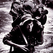 A Nicaraguan contra fords a small jungle river while on patrol near the border with Honduras.