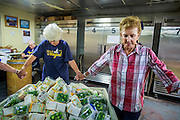 07 AUGUST 2012 - TOLLESON, AZ:  LUCY WOODRUFF, (checked shirt), the director of the food bank in Tolleson, AZ, joins the workers in prayer before the doors opened Tuesday. The Tolleson food bank has been operating for more than 20 years. It used to serve mostly the families of migrant farm workers that worked the fields around Tolleson but in the early 2000's many of the farms were sold to real estate developers. Now the food bank serves both farm worker families and people who lost their homes in the real estate crash, that his Phoenix suburbs especially hard. More than 150 families a day are helped by the Tolleson food bank, an increase of more than 50% in the last five years.    PHOTO BY JACK KURTZ