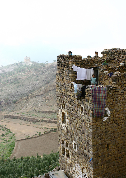 Al Hajjarah village, Jabal Haraz, Yemen. The stone houses in the mountains are like fortresses. Women have a their own floor specifically meant to welcome and entertain guests. <br /> Men have their own floor, too. The<br /> basement is reserved for livestock.