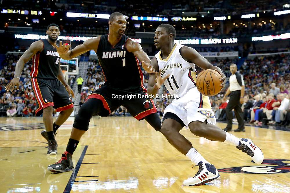 Oct 23, 2013; New Orleans, LA, USA; New Orleans Pelicans point guard Jrue Holiday (11) drives past Miami Heat power forward Chris Bosh (1) during the first half of a preseason game at New Orleans Arena. Mandatory Credit: Derick E. Hingle-USA TODAY Sports