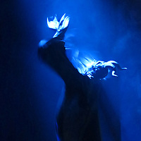 Monster figure in a haunted house full of smoke on Halloween night with light shinning from above and his arms raised.