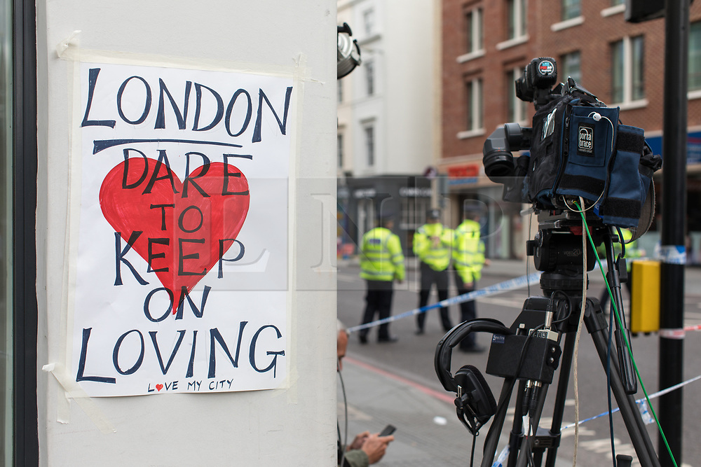 © Licensed to London News Pictures. 05/06/2017. London, UK. A sign which reads 'London: Dare to Keep on Loving' is pasted to a wall by a police cordon near Borough Market. Three attackers drove a van at pedestrians before stabbing a number of people in nearby bars on the evening Saturday 3 June 2017 in what police have described as a terrorist attack. Photo credit: Rob Pinney/LNP