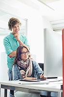 Businesspeople using desktop computer in creative office