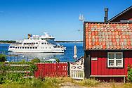 Waxholmsbåten Sandhamn utanför en röd stuga i Sandhamn i Stockholms skärgård
