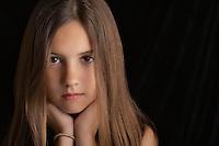 Girl (10-12) on black background portrait