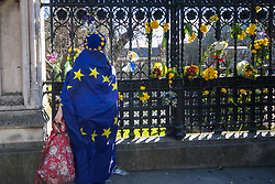 London, March 25th 2017. Tens of thousands of protesters in the Unite for Europe march against Brexit take to the streets of London just days after the Westminster terror attack in a show of defiance against extremism and Prime Minister Theresa May's 'hard Brexit'. PICTURED: A woman lays flowers at the railings around the Palace of Westminster in memory of those killed in Wednesday's terror attack on Westminster Bridge and Parliament.