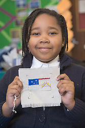 Primary school pupil holding up her handiwork during a sewing lesson at school,