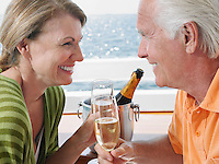 Middle-aged couple drinking champagne on yacht side view close-up