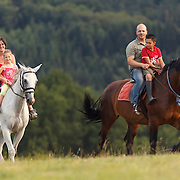 Man and a woman with kids on a horse in the country side