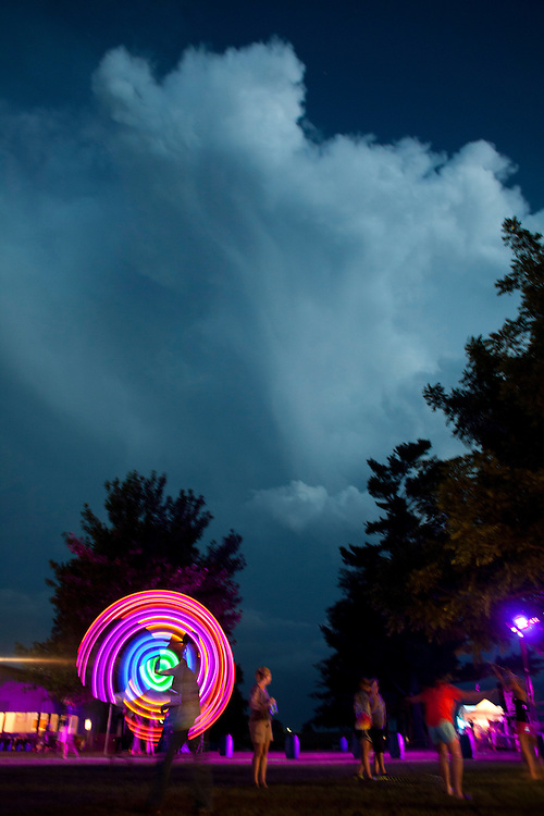 John Baldwin of Decorah plays with a glowing hoop as a storm rolls in at Camp Euforia on Thursday, July 16, 2015. Thursday was the first of three days of performances at the annual music fest, which is hosted by Jerry Hotz on his 120-acre farm north of Lone Tree in Johnson County.