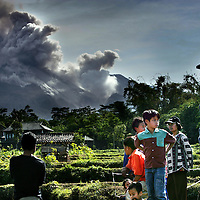 Indonesie.Jogjakarta.juni 2006.<br /> Bewoners uit de buurt van Jogjakarta kijken naar de aslawines die van de vulkaan de Mewati het dal instorten. De vulkaan is de laatste tijd erg actief en men vreest voor een grote uitbarsting.Vele mensen zijn al reeds geevacueerd.<br /> Foto:Jean-Pierre Jans
