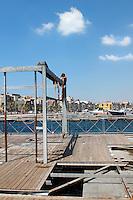 Bambino dedito a togliere la ruggine da una struttura precaria sul porticciolo della città vecchia di Taranto.
