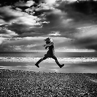 Woman leaps on a deserted beach with Storm clouds