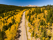 Aerial views of a mountain two-lane road in the fall color in the Colorado Rockies.