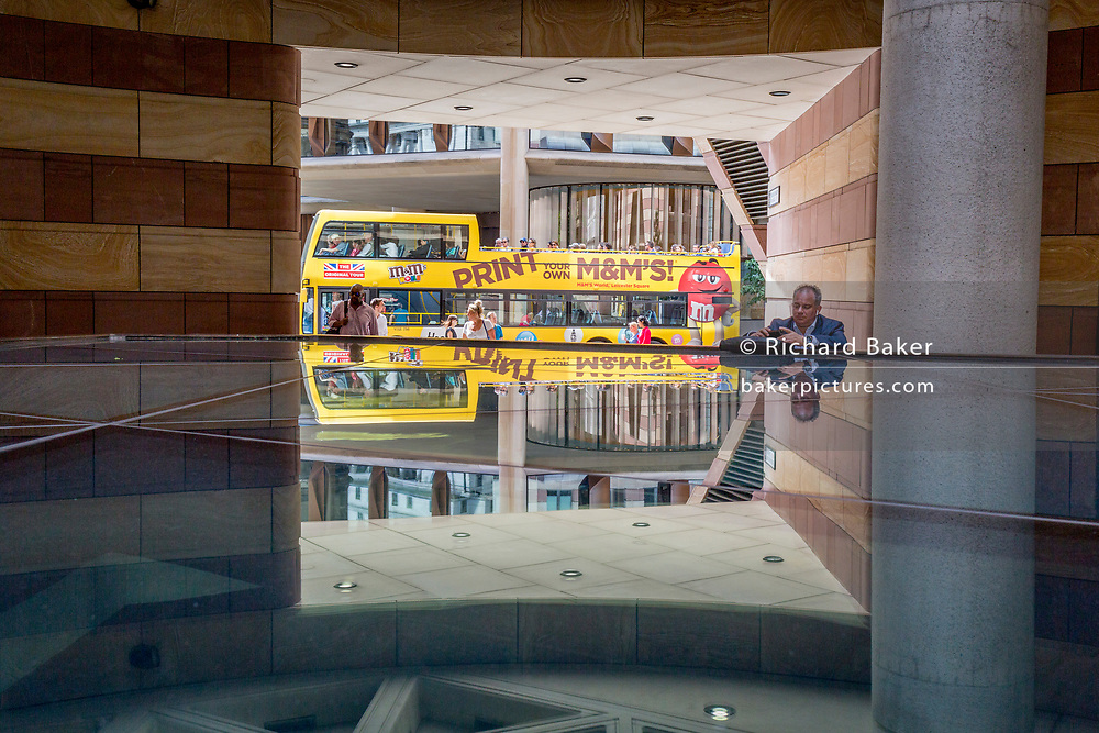 A tour bus passes the open architecture at number 1 Poultry towards the Bloomberg Building on Great Victoria Street in the City of London, the capital's financial district - aka the Square Mile, on 8th August, in London, England.