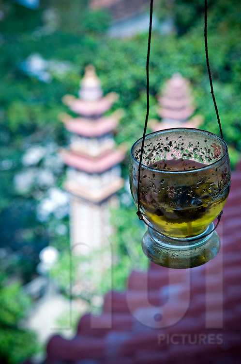 A small glass hangs in the air full of methylated spirits. Blurred pagoda pillar in background. Khanh Hoa area, Vietnam, Asia
