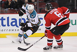 Oct 21; Newark, NJ, USA; San Jose Sharks left wing Jamie McGinn (64) skates with the puck while being defended by New Jersey Devils defenseman Andy Greene (6) during the first period at the Prudential Center.