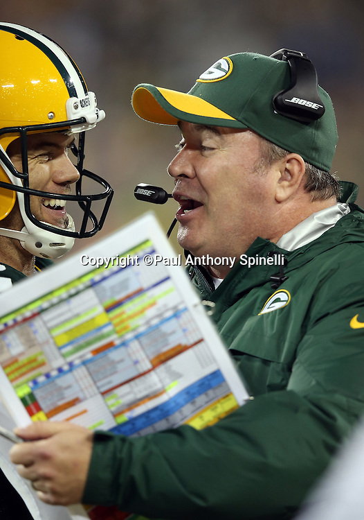 Green Bay Packers head coach Mike McCarthy has a hearty laugh with a player on the sideline during the 2015 NFL week 3 regular season football game against the Kansas City Chiefs on Monday, Sept. 28, 2015 in Green Bay, Wis. The Packers won the game 38-28. (©Paul Anthony Spinelli)