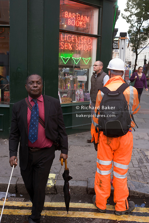 Surveyor dressed in orange high-vis suit stands outside Soho sex bookshop as unsighted man passes-by.
