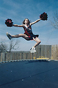 Portrait of Sandra Moffet jumping on a trampoline who is head cheerleader at Roby High school who won the Miss Rattlesnake round-up beauty pageant in Sweetwater, Texas, USA, 2003