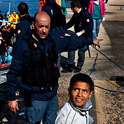 A boy who fled the unrest in Tunisia is helped by the Italian police after arriving at the southern Italian island of Lampedusa.An Illegal boat transporting nearly 140 immigrants approached the Island of Lampedusa. Despite the efforts of italian government who evacuated more 600 northen african refugees yesterday by the S. Marco ship, boats continues to attrack in the Island making the situation worser worser. The portual area of Lampedusa has become a second open air immigration centre where immigrants living  in critical igenic and sanitary conditions..