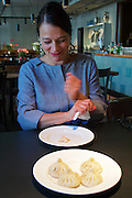 Vienna, Austria. Georgian Chinkali at Ansari restaurant.<br /> Nana Ansari shows how to eat them.