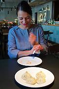 Vienna, Austria. Georgian Chinkali at Ansari restaurant.<br /> Nana Ansari shows how to eat them.