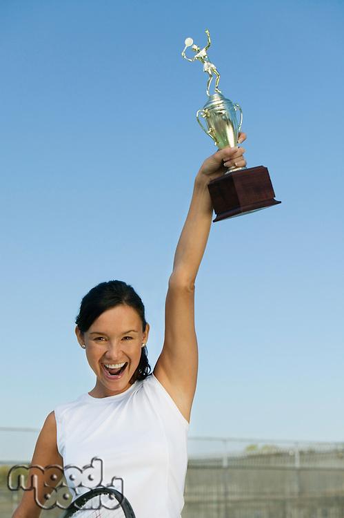 Tennis Player Holding Trophy Aloft