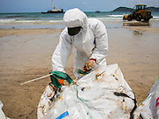 02 AUGUST 2013 - KOH SAMET, RAYONG, THAILAND: Workers seal plastic bags full of contaminated cleaning products on Ao Prao beach on Koh Samet island. About 50,000 liters of crude oil poured out of a pipeline in the Gulf of Thailand over the weekend authorities said. The oil made landfall on the white sand beaches of Ao Prao, on Koh Samet, a popular tourist destination in Rayong province about 2.5 hours southeast of Bangkok. Workers from PTT Global, owner of the pipeline, up to 500 Thai military personnel and volunteers are cleaning up the beaches. Tourists staying near the spill, which fouled Ao Prao beach, were evacuated to hotels on the east side of the island, which was not impacted by the spill. Officials have not said when Ao Prao beach would reopen. PTT Global Chemical Pcl is part of state-controlled PTT Pcl, Thailand's biggest energy firm.    PHOTO BY JACK KURTZ