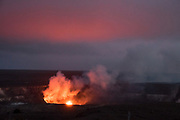 """Magenta twilight over Halemaumau lava lake glowing in Kilauea. Halema'uma'u Crater is an active pit crater containing a steaming lava lake, within the much larger summit caldera of Kilauea in Hawaii Volcanoes National Park on the Big Island, Hawaii, USA. With its name meaning """"house of the 'ama'u fern,"""" Halemaumau is home to Pele, goddess of fire and volcanoes according to Hawaiian mythology. Established in 1916 and later expanded, the park (HVNP) encompasses two active volcanoes: Kilauea, one of the world's most active volcanoes, and Mauna Loa, the world's most massive shield volcano. The park portrays the birth of the Hawaiian Islands with dramatic volcanic landscapes, native flora and fauna, and glowing flowing lava. HVNP is honored as a UNESCO World Heritage Site and International Biosphere Reserve."""