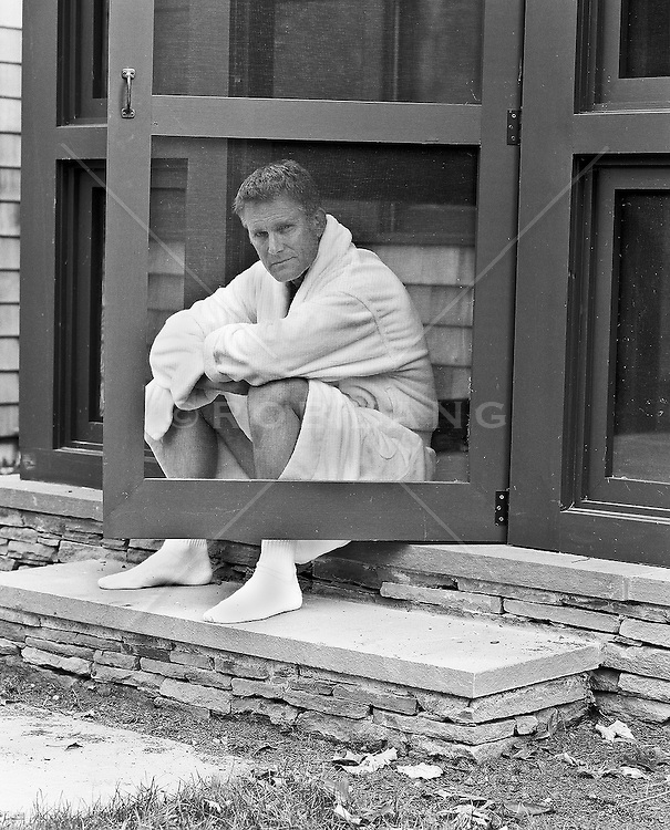 Mature man wearing a white bathrobe sitting on a step behind an open screen door
