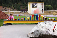 Johanna Dickert, 2, plays near a display for mining display where a clean-up and restoration project at the site of the Wallace railway yard is currently taking place. As each section of the site is completed, the area is transformed into a public use area.