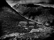 Stone cabins to shelter local pastoralists in harsh weather that is common in the Swiss Alps, even in summer in the high pastures like this one.  Life has always been hard up high among Switzerlands glaciers.  Add to that climate change and the changing economy, but still somehow many of the time-tested traditions, like animal husbandry hold on into the present day.  Above the tree line between the Great Aletsch and Fiescher Glaciers, Oberes Talli, Switzerland.