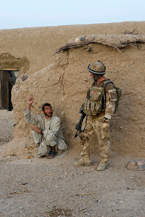 British soldiers of 3rd Battalion The Parachute Regiment guards an Afghan man during a dawn assault on a compound as part of Operation 'Southern Beast'. Kandahar Province, Afghanistan on the .th of August 2008.