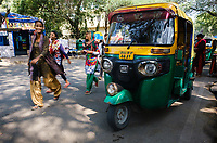 NEW DELHI, INDIA - CIRCA NOVEMBER 2018: Auto Rickshaw, alos called Tuk Tuk in the street of New Delhi, The green and yellow taxis are a common sight in the streets of Delhi and a popular tourist mode of transportation.