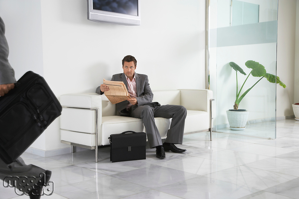 Man reading newspaper waiting in office hallway