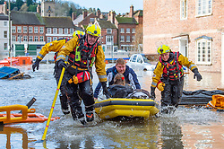 © Licensed to London News Pictures. 26/02/2020. Bewdley, UK. A girl and man in a small inflatable rescue boat are brought to safety in the village of Wribbenhall on the eastern side of the Severn in Bewdley. Photo credit: Peter Manning/LNP
