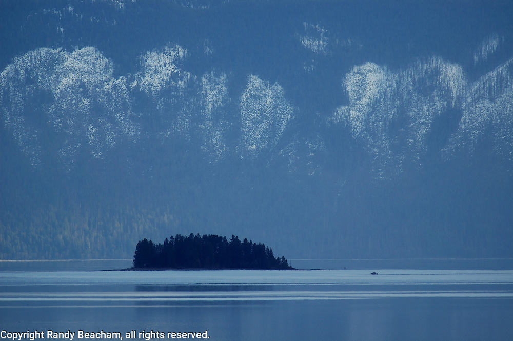 Lake Pend Oreille with island and fishing boat at sunset. Near Hope, north Idaho.