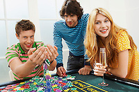 Young man with friends at roulette table playing with chips portrait