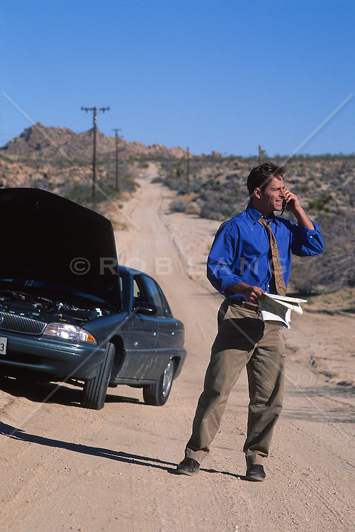 businessman calling for help in the desert by broken down car