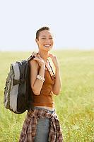 Female hiker standing in field portrait